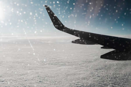 View of the morning winter sky through a frozen window of an airplane. Aerial background with a copy space Standard-Bild