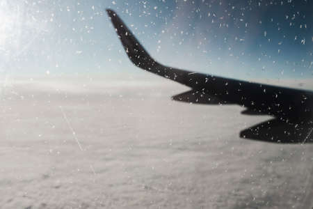 View of the morning winter sky through a frozen window of an airplane. Aerial background with a copy space.