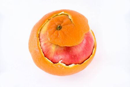 Red apple on white background appearing under peeling of mandarin.