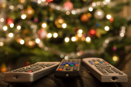 Three remote controls in foreground of christmas tree with lights, colorful decorations and balls. Full of wellbeing, peace, coziness and relaxing mood on Christmas Eve. But also gently reflecting modern time with many technical devices, stress and strain