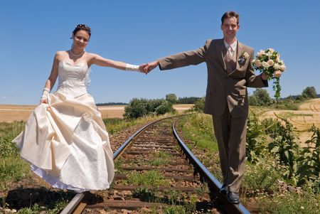Bride and groom holding hands and balancing on rails Stock Photo