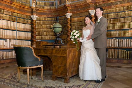 Bride and groom standing in ancient library with old globe, chair and wooden shelfs with books