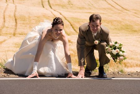crouched: Bride and groom are crouched on starting line and ready for their new life. Golden field is used as background, groom is holding flowers.