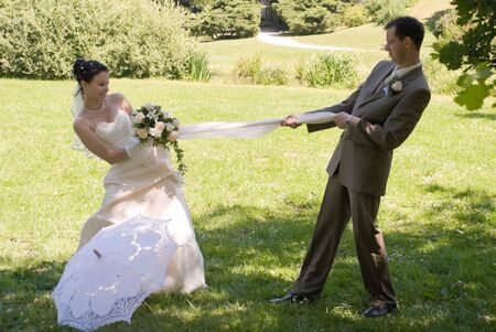 Bride and groom are fighting for veil. Green background, white decorated umbrella in foreground. photo