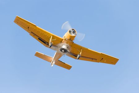 piloting: Small yellow duster airplane on clear blue sky Stock Photo