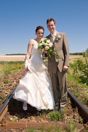 Bride and groom holding hands and flowers standing in rails with blue sky as background photo