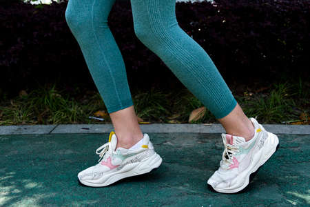Woman wearing white sneakers leg's close up Imagens