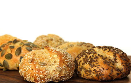 Various types of bread rolls on a wooden board