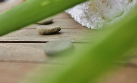 aloe vera, flat stones and a rolled towel on wood Stock Photo