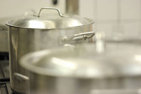 Steaming pots made of stainless steel in a commercial kitchen on the stove.