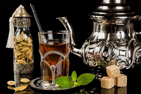 cardamon: Arabic mint tea and cardamon seeds on the black background