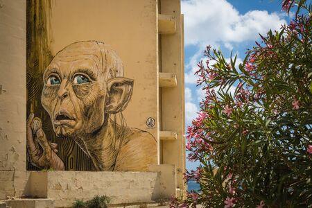 glum: Marsaskala, Malta - 03 May 2016: Portrait of Gollum from Lord of the Rings fantastic story. Graffiti on a building under construction. Editorial