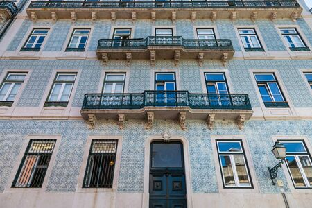 Typical decoration of the facade of the house in Lisbon. Traditional ceramic tiles azulejos. Stock Photo