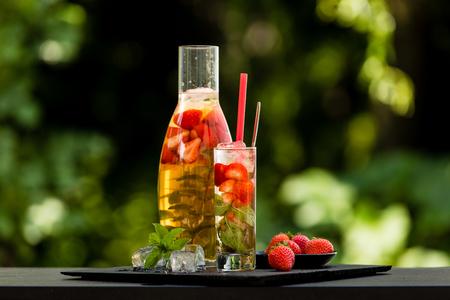 lemon balm: Homemade strawberry ice tea in the garden. Strawberries, mint and lemon balm leaves, ice and green tea. Stock Photo