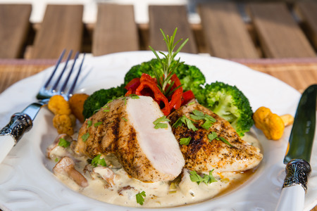 Grilled chicken, cream sauce with mushrooms chanterelles, broccoli and roasted red peppers. Healthy balanced food concept.