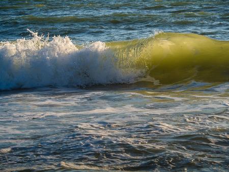 Las olas del Atlántico se iluminan con la puesta de sol. Gale en la costa meridional portuguesa del Atlántico. Foto de archivo