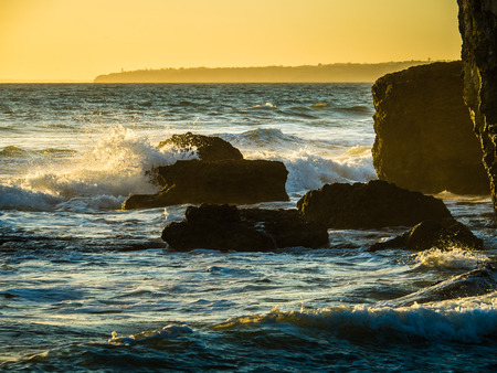 amanecer: The waves of the Atlantic are lighted by the sunset. Gale on the southern Portuguese coast of the Atlantic.