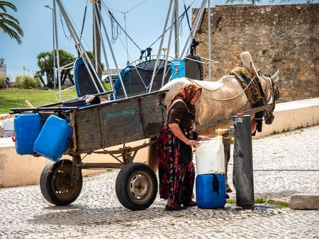 Lagos, Portugal - Jun 18, 2018: Old woman came to draw drinking water. Lagos, Algarve, Portugal