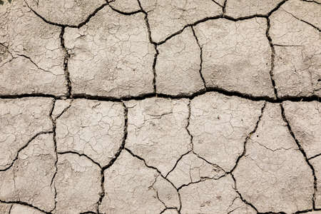Dry cracked soil. The fields are missing rain. Stock Photo
