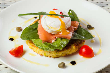 Poached egg with salmon, tomato, and baby spinach on a light background photo