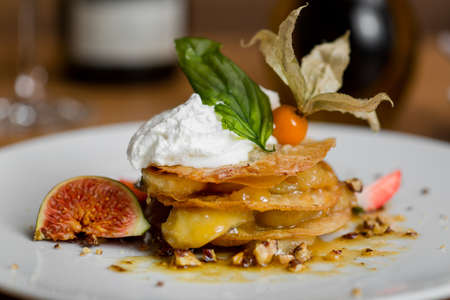 winter cherry: dessert of puff pastry with fruit, figs, winter cherry, walnuts and whipped cream on a white plate