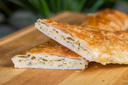 unleavened: baking of unleavened dough, with cheese and dill on a wooden board
