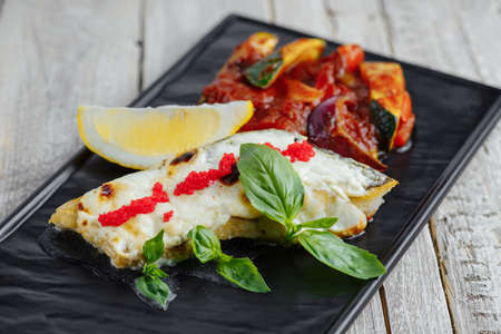 lunch tray: Fried fish in batter with lemon on a black tray on a wooden table Stock Photo