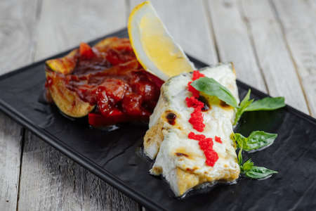 lunch tray: fish in batter with caviar crab, lemon and spices on a black tray on a wooden table