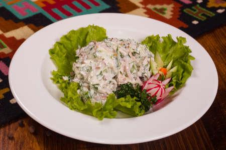 ensaladilla rusa: Una deliciosa ensalada y lechuga en un plato blanco Foto de archivo