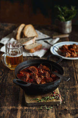 national dish in a cauldron of broth and meat with spices on an old rustic table, sliced bread