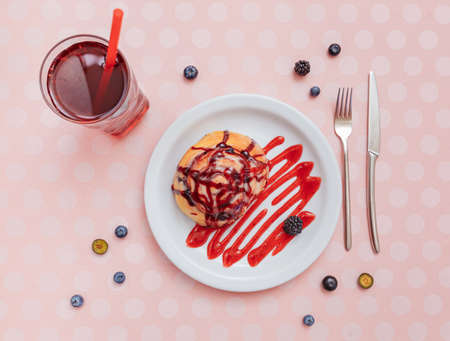 bright composition top view on a plate fresh cinnabon poured with strawberry syrup next to a glass of juice, laid out berries, fork and knife