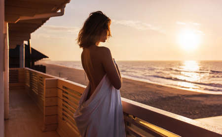 half-naked girl stands wrapped sheet with her back to the frame on the terrace at dawn on the beach Banque d'images