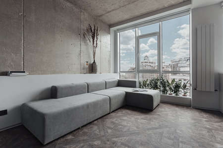 the living room with a long grey sofa near the panoramic window, the walls are decorated as a concrete surface. Minimalist decor, room plants by the window