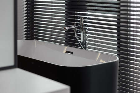 Luxury mixer and blinds in a beautiful grey bathroom. Bathroom fragment. Modern bathroom design