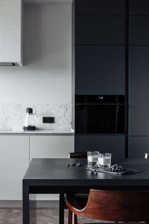 helle Küche mit dunklem Tisch, praktische Lage von Küchenzubehör und -geräten, moderner Stil, weiße Wände, Marmorarbeitsfläche und Parkettboden. Auf dem Tisch steht ein Glas Milch und eine Blaubeere Standard-Bild