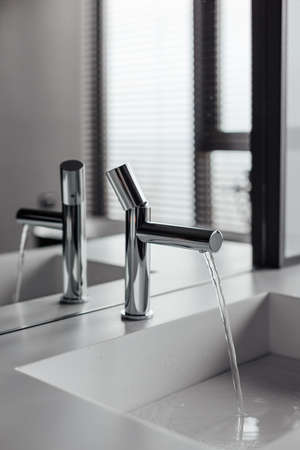 A luxurious mixer and blinds in a beautiful grey bathroom. Sanitary prophylaxis of the antiviral concept.