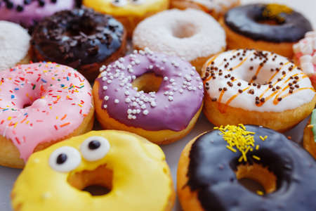 A lot of multi-colored donuts with different fillings, top view Imagens