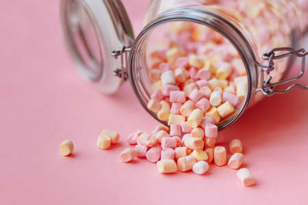 sprinkled marshmallows from a glass jar on a pink background. Tilted glass jar with a lid. White marshmallows Imagens