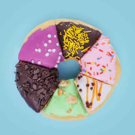 A donut consisting of slices of six different donuts on a pale blue background. Coffee and donuts in the morning