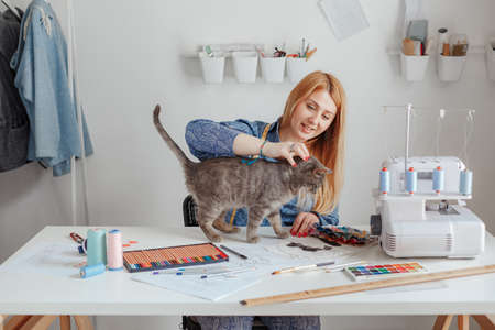 the young designer creates the eksikzy in his studio and strokes the cat, a small business, the tailor works at home on the order. The cat came to help the owner. Sews clothes Imagens