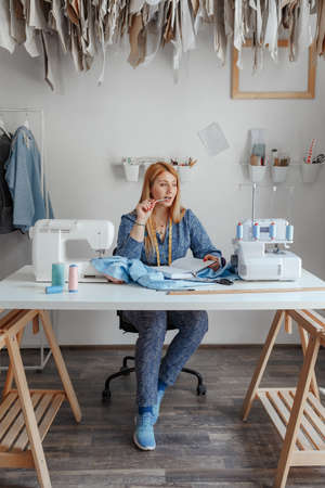 Portrait of happy young lady fashion designer smiling standing in workshop alone looking at camera. Small business owner and successful youth concept. You can see the thread, sketches, the fabric and the tool of the tailor Imagens