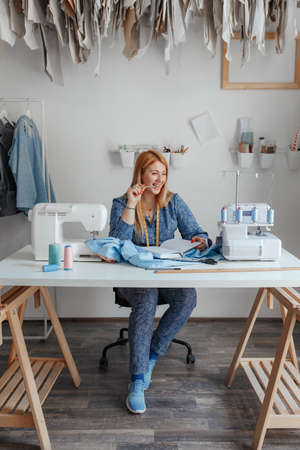 Portrait of a happy seamstress working in her sewing studio. woman seamstress, fashion designer thought and smiles while working on fabric in the Studio workshop.