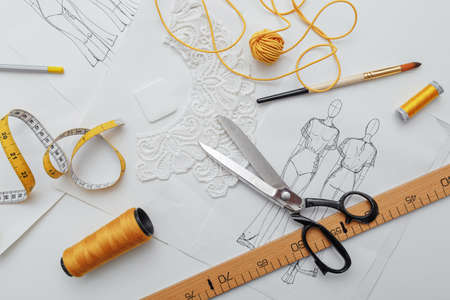 tailors tools laid out on a table, scissors and a centimeter, sketches and threads in yellow and white. sewing workspace