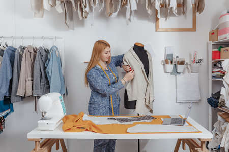 young clothes designer in her studio. Fashion designers at work. tailor working on customers dress in clothing design studio.