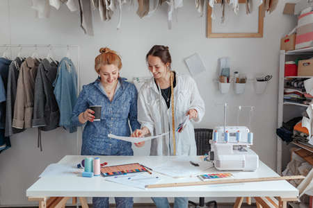 Fashion designer sewing fabrics with assistant. two young designers work in a bright studio, have opened their own business and are ready to take orders. Beginning of work