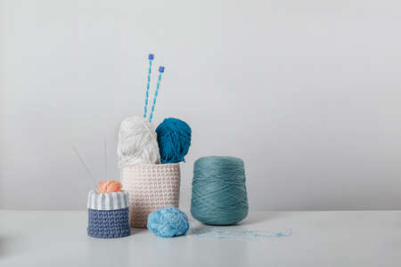 composition of threads and rollers on a white background. Knitting kit