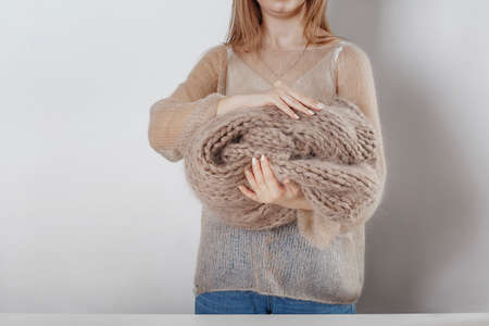 woman holds in hands knitting beige sweaters Imagens