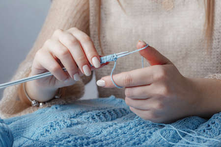 hands of woman are knitting blue jersey at the table
