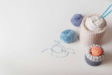 Wool yarn in coils with knitting needles in wicker basket on white background