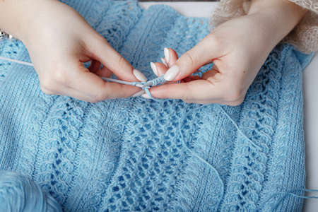 hands of young woman makes knitting sweater